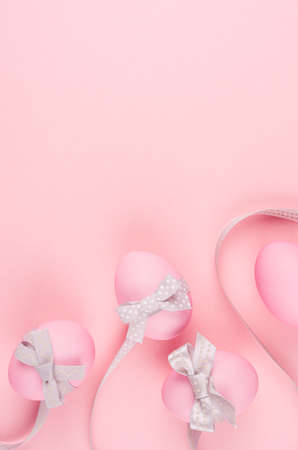 Pink easter eggs with gray curved ribbons on pastel pink background, vertical, stories. 免版税图像 - 167087259