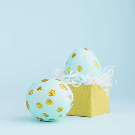 Elegant easter eggs with gold dots and golden gift box on blue background, square.