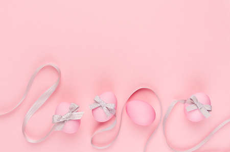Fashion easter background - pink eggs with gray ribbon quaint stripes as border on pastel pink color. 免版税图像
