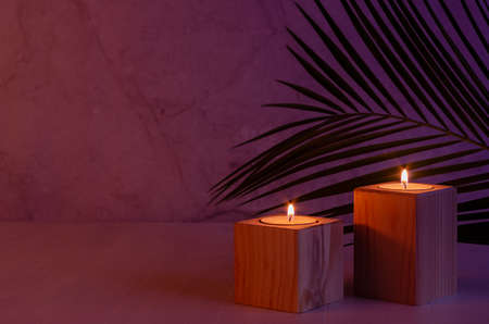 Romantic home decor in tropical style with burning candles and palm leaf in evening purple and orange light, copy space. 免版税图像