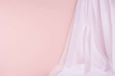 Soft light scene with airy folded white silk curtain on pastel pink wall. Abstract background.