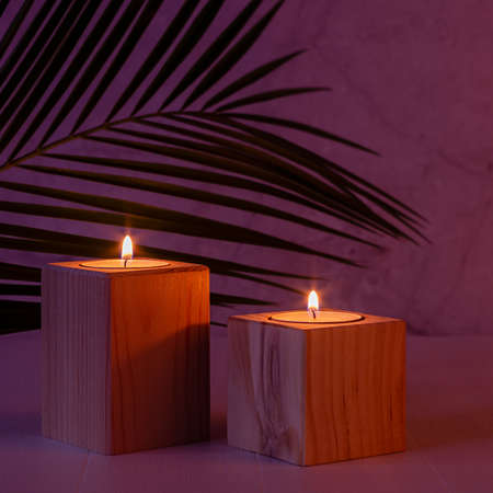 Night tropical atmosphere for vacation and relaxation with burning candles and palm leaf in purple orange sunset light, square.