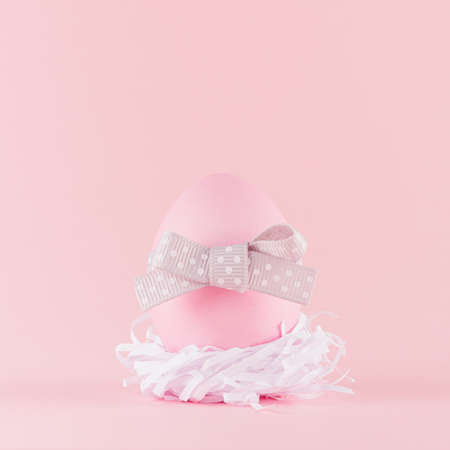Cute naivety easter background with pink egg with gray bow in white nest on pastel pink backdrop, square. 免版税图像
