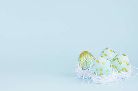 Bright easter background - blue eggs with golden design in white nest on blue backdrop, copy space.