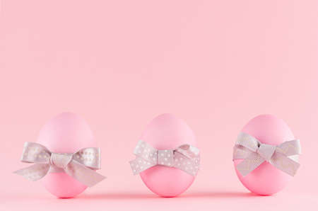 Pink easter eggs with gray bows standing in row on pastel pink background. 免版税图像