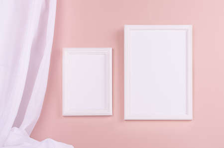 Modern simple gallery with set of blank rectangle photo frames for text, design or pictures with folded silk curtain hanging on pastel pink wall. Template for display and portfolio.