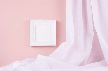 Modern simple gallery with blank square photo frame for text, design or pictures with folded silk curtain hanging on pastel pink wall. Template for display and portfolio.