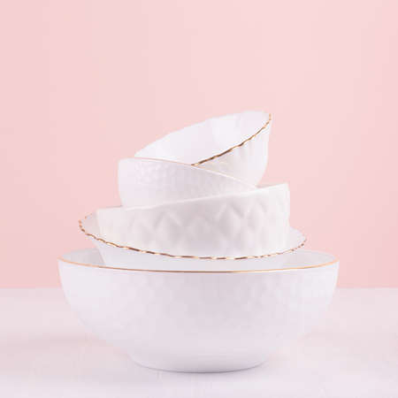 White ceramic crockery with thin gold line, textures in elegant soft light pink interior on white wood table, square. Airy delicate fashion bowls as home decor. 免版税图像