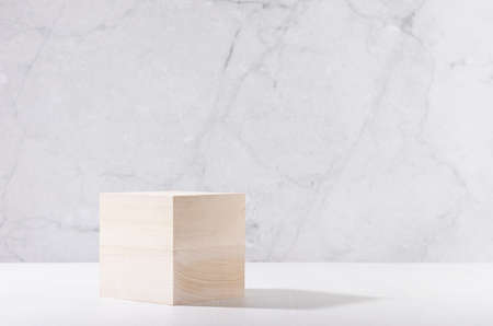 Minimal modern showcase with wooden cube podium on white board and gray marble wall for cosmetics product display.