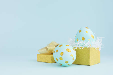 Fashion easter background - blue eggs with golden dots and opened gift box on blue color.