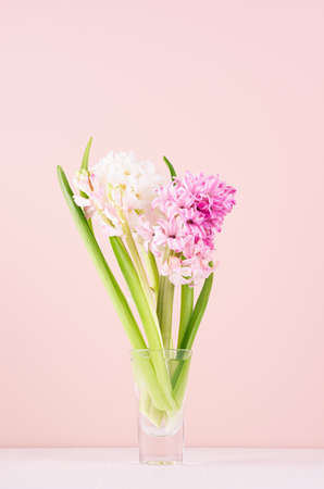 Elegant tender pink hyacinth bouquet for mothers day on white wood table, copy space, vertical.