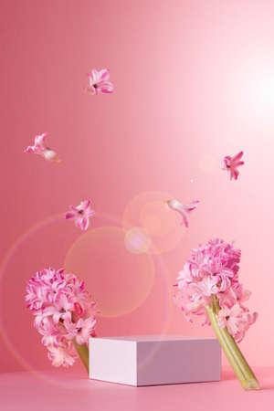 Tender delicate spring mock up with white square podium for presentation cosmetic, produce, fresh flowers hovering on sunny soft light pink background, vertical. 免版税图像
