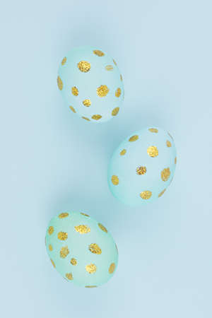 Festive easter background - blue easter eggs with golden glitter dots on blue backdrop, closeup, vertical. 免版税图像