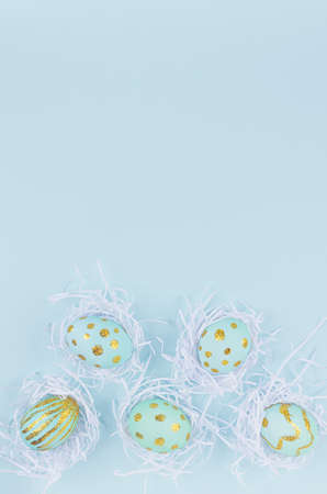 Festive easter background - blue easter eggs with golden glitter design in white nest as border on blue, copy space, top view, vetical.