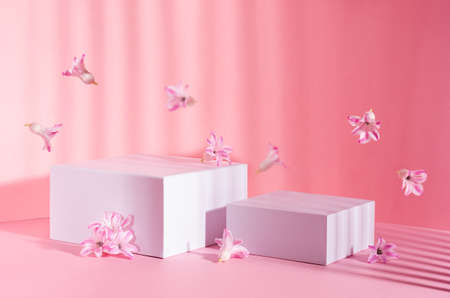 Set of two white square podiums for presentation cosmetic and produce in sunbeam with striped shadow with spring flowers flying on soft light pastel pink background.