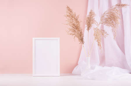 Soft pastel pink interior with blank photo frame, white silk curtain and beige fluffy reeds on wood shelf, copy space.