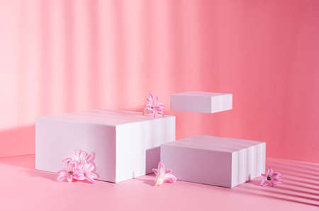 Fashion pastel pink mock up with set of white square podiums for presentation cosmetic, accessories and produce in sunlight with levitate spring hyacinth flowers.