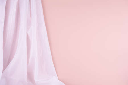 Delicate home decor with flow silk curtain on pastel pink wall. Mock up for portfolio, design or text.