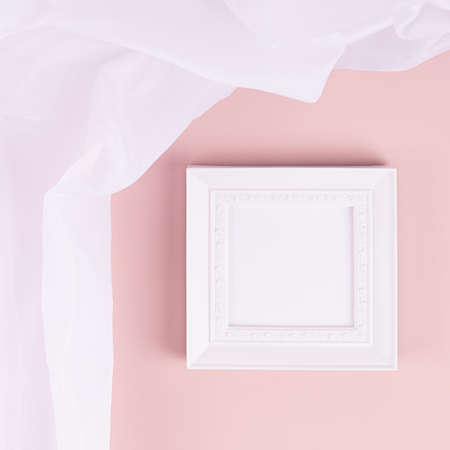 Abstract pastel pink interior with white blank square photo frame for text, design, poster, pictures with flow silk curtain on pastel pink wall. Mock up for display portfolio. 免版税图像