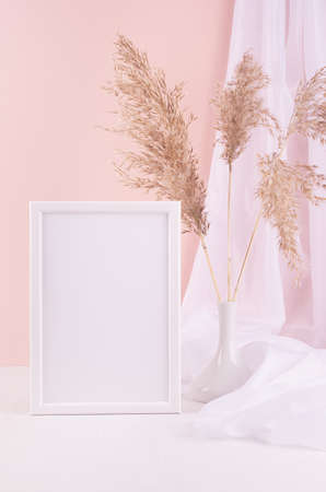 Delicate home decor with blank wooden poster frame, silk curtain and fluffy reeds in vase on white wooden table, pastel pink wall, vertical. Mock up for portfolio.