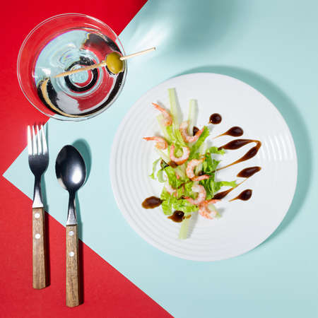 Fresh summer salad of shrimps, greens, celery, teriyaki sauce with cutlery, with martini glass on red and minty color with shadow in sunlight, square. Colorful modern geometric style food background.