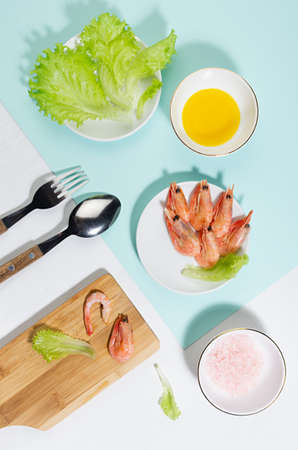 Spring fresh salad of shrimps, greens, oil, pink salt - ingredients in bowl on cutting board on mint color with shadow in sunlight. Colorful modern geometric style of food background, vertical.