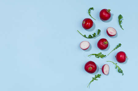 Radish and arugula with shadow on blue background as border, top view, copy space. Colorful spring vegetable background.