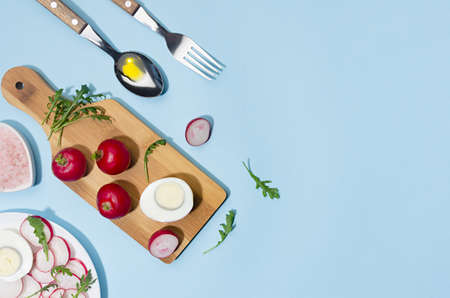 Recipe of organic salad of radish, arugula and eggs with olive oil on blue background, flat lay, copy space. Modern concept with shadow and hard light.
