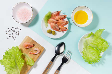 Healthy lifestyle - cooking of fresh salad of prawn, green salad, olive, black pepper, pink salt in sunlight with shadow, flat lay, on white wooden table, minty background.