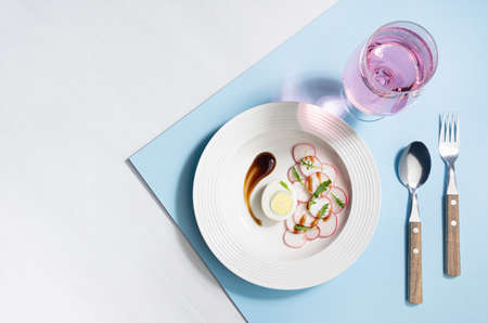 Colorful organic salad of radish, arugula, eggs with balsamic sauce with rose sparkling wine in glass on blue background, top view, border. Modern concept with shadow and hard light. 免版税图像