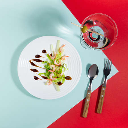 Spring seafood salat of shrimps, greens, celery, balsamic sauce with martini cocktail in white plate on red and minty color background with shadow in hard light, top view, square. 免版税图像