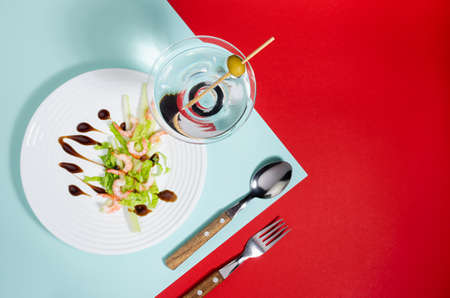 Fresh summer salad of shrimps, greens, celery, teriyaki sauce with cutlery, with martini glass on red and minty color with shadow in sunlight. Colorful modern geometric style food background.