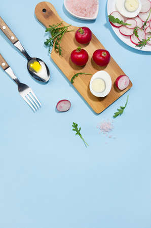 Healthy lifestyle - cooking of spring salad of raw fresh vegetables - radish, arugula with eggs in sunlight with shadow, top view, vertical, on white wooden table, blue background. 免版税图像