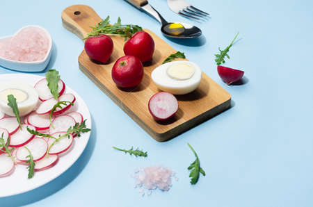 Healthy lifestyle - cooking of spring salad of raw fresh vegetables - radish, arugula with eggs in sunlight with shadow, border, on white wooden table, blue background.