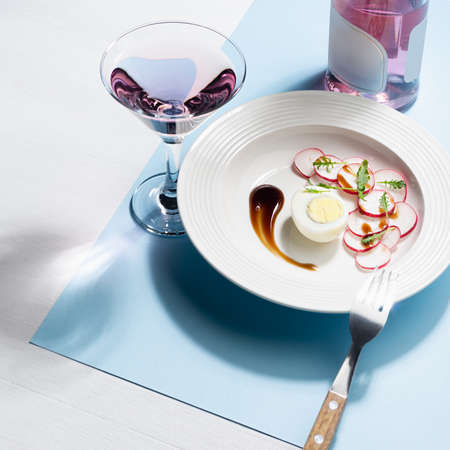Fresh salad of radish, arugula and eggs with teriyaki sauce art plating, glass of rose wine, bottle, cutlery on white wood table, blue color with shadow in sunlight, square. Colorful geometric style food background.