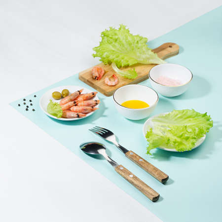 Dieting salad of fresh greens, shrimps with shadow in hard light on pastel mint color and white wood table, square. Summer healthy food in color modern style.