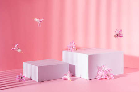 White square podiums for display cosmetic, products in sunlight with spring flowers flying and striped shadow in sunny day on pink background, copy space.