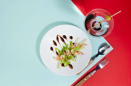 Colorful organic salad of shrimps, greens, celery, balsamic sauce with cocktail decorated green olive on red, minty background, flat lay. Modern concept with shadow and hard light. 免版税图像