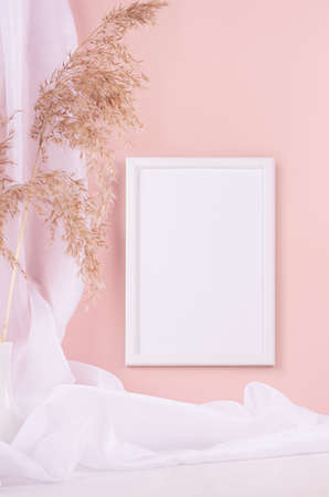Calm pastel interior with white decoration - blank frame for poster, text or design hanging on pink wall, fluffy reeds, curtain on white wood table, vertical. 免版税图像