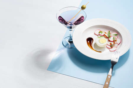 Colorful organic salad of radish, arugula, eggs with balsamic sauce with fresh pink cocktail on blue background, border. Modern concept with shadow and hard light. 免版税图像