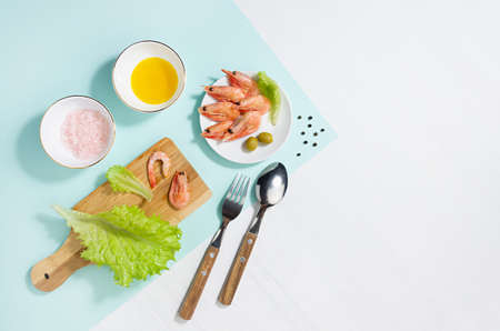 Fresh summer vitamin appetizer of green salad, shrimps, olive with shadow in sunlight on white wood table, minty background, copy space. Seafood salad ingredients and cooking.