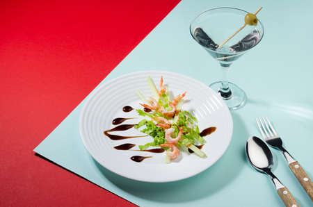 Modern cuisine - seafood salad with greens and teriyaki sauce with cocktail decorated green olive on red and mint color background, copy space.