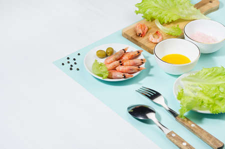 Spring fresh salad of shrimps, greens, oil, pink salt - ingredients in bowl on cutting board on mint color with shadow in sunlight. Modern geometric style of food background, border.