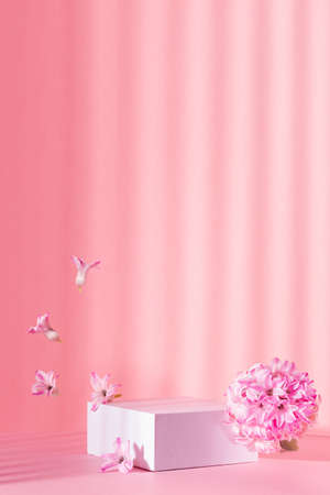 White square podium for presentation cosmetic, accessories and produce on sunny bright pastel pink background with striped shadows, levitate spring hyacinth flowers, vertical.