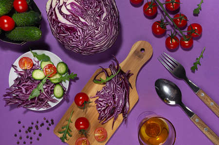 Cooking of fresh summer vegetable salad with red cabbage, cherry tomato, cucumber, arugula and oil with shadow in sunny day on purple background. 免版税图像