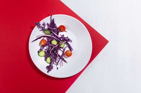 Fresh summer vegetable salad with red cabbage, cherry tomato, cucumber with shadow in sunny day on red color, white wood table, top view.