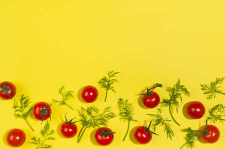 Fresh red tomato and green dill with shadow as border on yellow background, modern food pattern, top view.