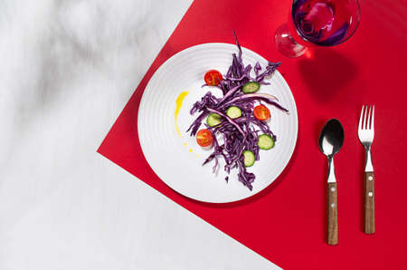 Fresh summer vegetable salad with red cabbage, cherry tomato, cucumber, oil, drink in glass with shadow in sunny day on red color, white wood table, top view. 免版税图像