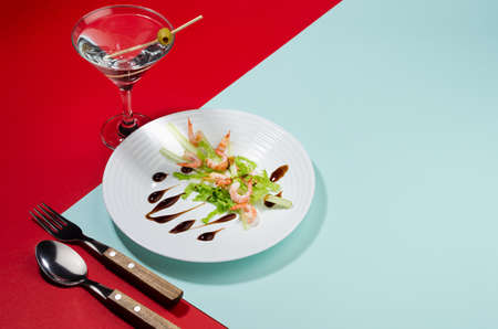 Modern elegant geometric style in food - appetizer of shrimps, greens, celery, teriyaki sauce with martini cocktail with shadow in sunlight on red and minty background, border. 免版税图像