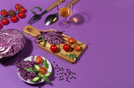 Ingredients for cooking of fresh summer vegetable salad with red cabbage, cherry tomato, cucumber in hard light on purple background, flat lay. 免版税图像
